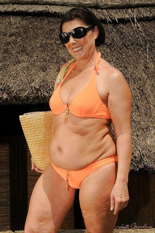 Chubby mature brunette in sunglasses taking off her bikini outdoor