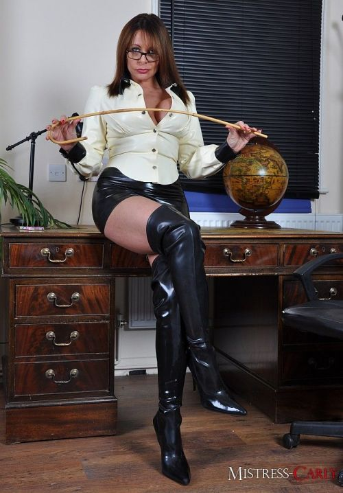 Older Domme Mistress Carly spanks mans bare ass in short skirt and long boots